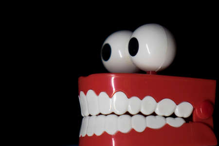 A smiling toy prosthesis, with white teeth and large eyes isolated against a black background.