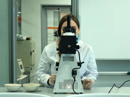 A young woman in a white uniform is working in a laboratory behind a microscope .
