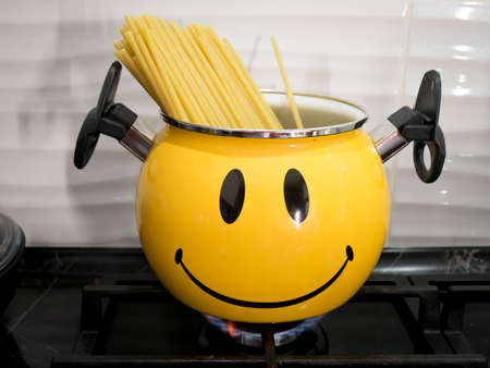 The spaghetti is cooked in a pot on the stove in the kitchen.