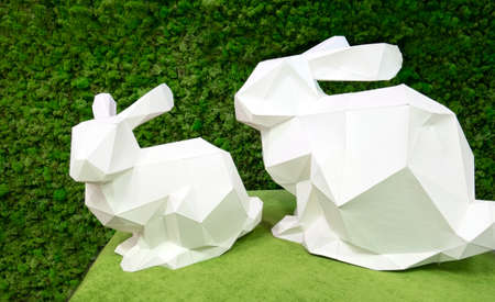 White paper rabbit on a background of green moss. Easter bunnies origami .