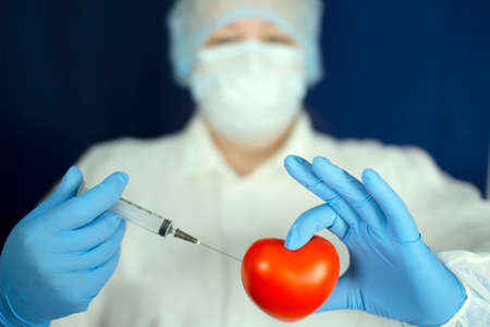 The heart and the syringe are in the doctors hands. Zdjęcie Seryjne