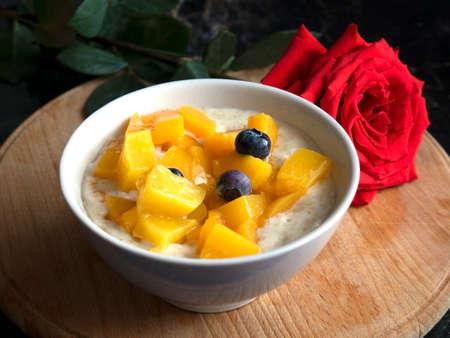 Oatmeal porridge with blueberries. Lovely breakfast with rose