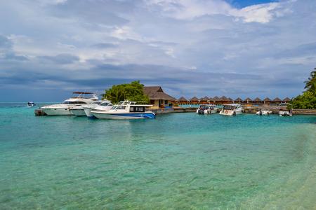 atoll: Atoll, Maldives - November 18, 2014: Pier with boats - transfer from airport