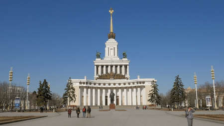 people are walking in front of main pavilion of VDNKh, Moscow in sunny day