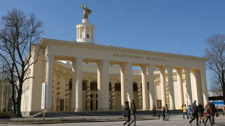 people are walking in front of pavilion Belarus in VDNKh, Moscow in sunny day