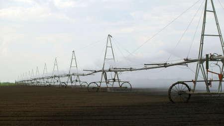 Sprinkler irrigation system in field Banco de Imagens