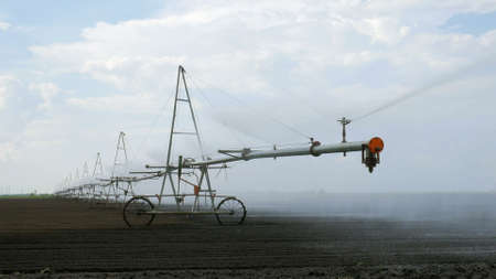 Sprinkler irrigation system is sprinkling water in a field