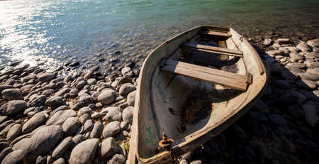 wooden boat on the shore of a mountain river
