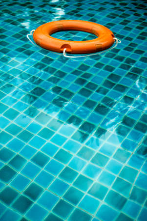 orange lifebuoy in pool water