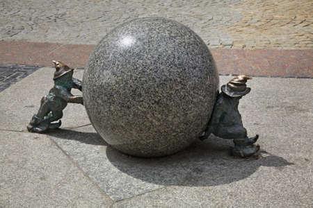 sisyphus: Gnomes (Krasnoludki) Syzyfki push the ball. Wroclaw. Poland