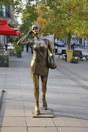 Sculpture of a girl with a phone in Skopje. Macedonia Editorial