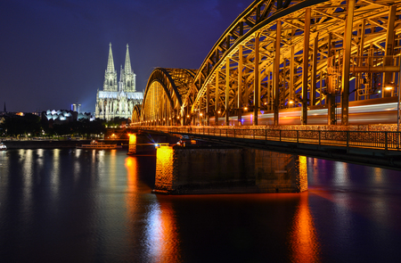 Night panorama of Cologne, Germany, with the river Rhine, the railway Hohenzollern Bridge and Cologne Cathedral, a famous landmark and a largest gothic church in Northern Europe
