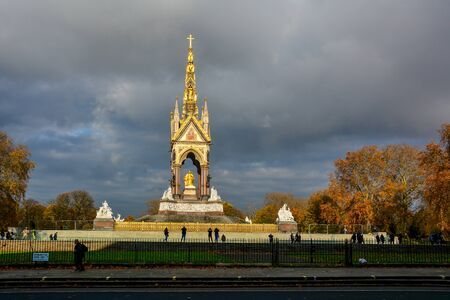 Albert Memorial outside the Royal Albert Hall in Kensington Gardens, London, UK, with the dramatic sky and yellow autumn trees