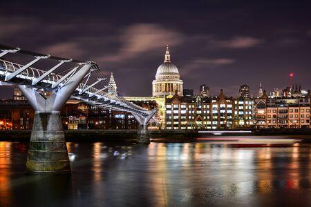 Belle vue nocturne sur le dôme illuminé de la cathédrale St Paul dans la ville de Londres, Londres, Royaume-Uni, avec la Tamise et le Millennium Bridge moderne