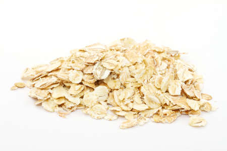Heap of dry rolled oats isolated on white background photo