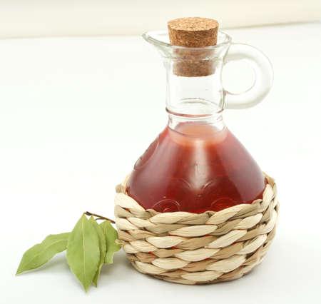 hoja de botella y laurel de vinagre en el blanco Foto de archivo