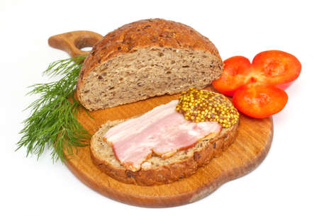 vespers: Bread with ham, mustard, dill and tomato on the wood plate