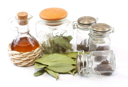 vinegar bottle, spices and laurel leaf on the white photo