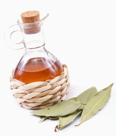 vinegar bottle and laurel leaf on the white
