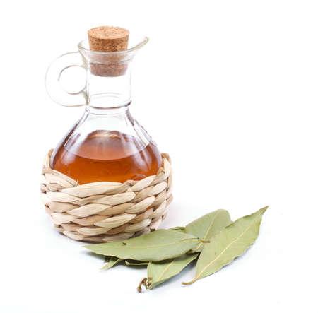 vinegar bottle and laurel leaf on the white photo