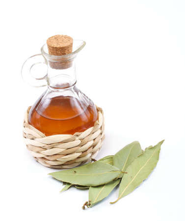 vinegar bottle and laurel leaf on the white photo