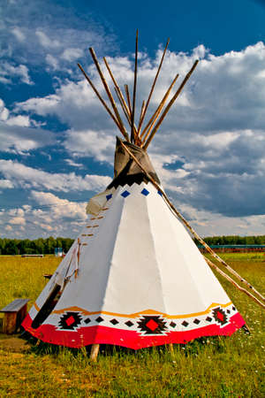 An indian teepee set up in a meadow among pine woods (portrait orientation). Redakční