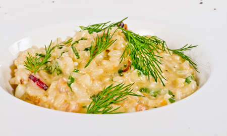 photo of delicious risotto with seafood and dill on it photo