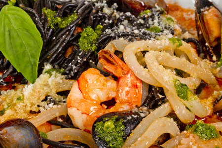 Black tagliatelle (pasta made with cuttlefish ink) with shrumps, mussel and squid photo