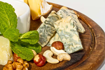 Various types of cheese with honey, nuts and grapes on plate, isolated on white photo