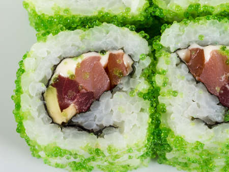 fish type: Tobiko Spicy Maki Sushi - Hot Roll with various type of Tobiko (flying fish roe) outside. Tuna, avocado and Green Lettuce inside