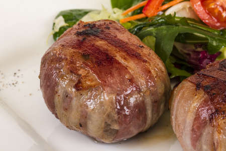 filets: Grilled steak wrapped in bacon, with grilled vegetables, mashed potatoes