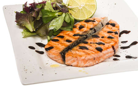 savory fish portion : roasted norwegian salmon fillet garnished with salad and basil leaves and lime on white dish isolated with balsamic sause Stock Photo - 13634148