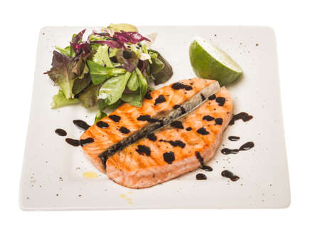savory fish portion : roasted norwegian salmon fillet garnished with salad and basil leaves and lime on white dish isolated with balsamic sause Stock Photo - 14034647