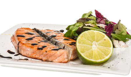 savory fish portion : roasted norwegian salmon fillet garnished with salad and basil leaves and lime on white dish isolated with balsamic sause Stock Photo - 14034784