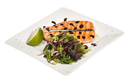 savory fish portion : roasted norwegian salmon fillet garnished with salad and basil leaves and lime on white dish isolated with balsamic sause photo