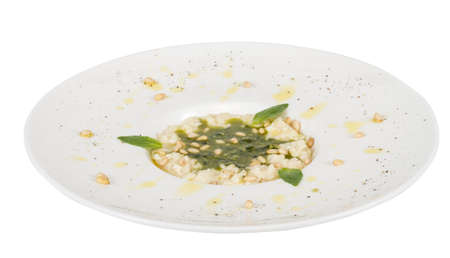 photo of delicious risotto dish with herbs and cedar nut on white background photo