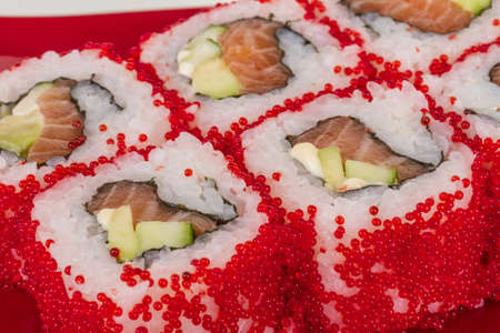 fish type: Tobiko Spicy Maki Sushi - Hot Roll with various type of Tobiko (flying fish roe) outside. Salmon, avocado and Green Lettuce inside