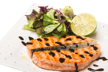 savory fish portion : roasted norwegian salmon fillet garnished with salad and basil leaves and lime on white dish isolated with balsamic sause Stock Photo - 14069069
