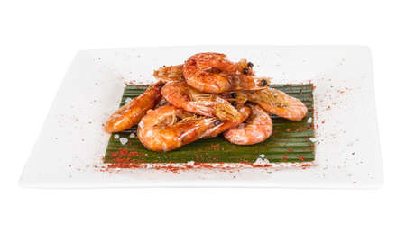 fried black tiger prawns with herbs and spices on banana leaf photo