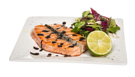savory fish portion : roasted norwegian salmon fillet garnished with salad and basil leaves and lime on white dish isolated with balsamic sause Stock Photo - 14427510