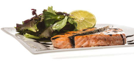 sause: savory fish portion : roasted norwegian salmon fillet garnished with salad and basil leaves and lime on white dish isolated with balsamic sause