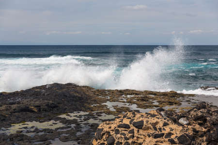 Turbulent ocean waves with white foam beat coastal stones photo