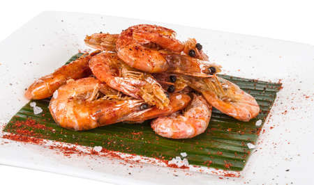 gambas: fried black tiger prawns with herbs and spices on banana leaf