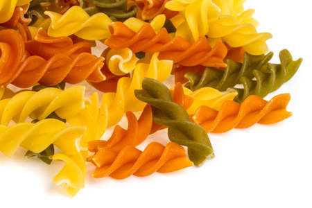 Uncooked pasta fusilli in different colours, white background photo