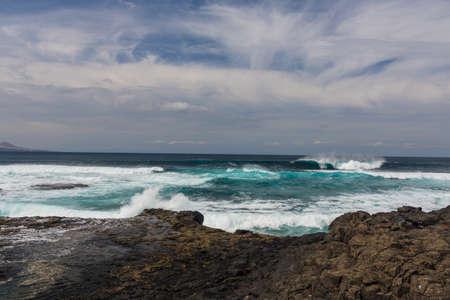 turbulent: Turbulent ocean waves with white foam beat coastal stones