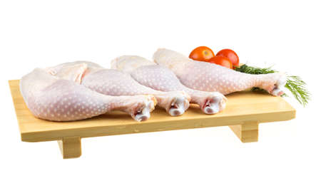 Fresh raw chicken wings on chopping board with roma tomatoes photo