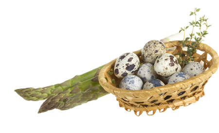 quail eggs in a basket with raw asparagus photo