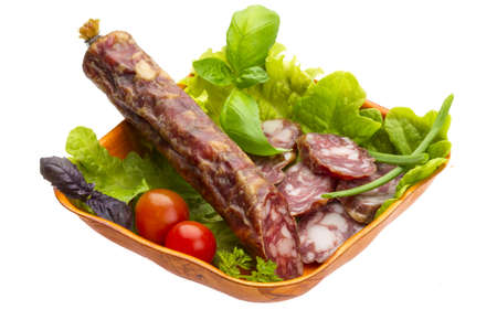 Ripe salami with salad, basil, onion and tomato photo