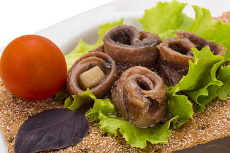 Anchovy snack with salad and tomato photo