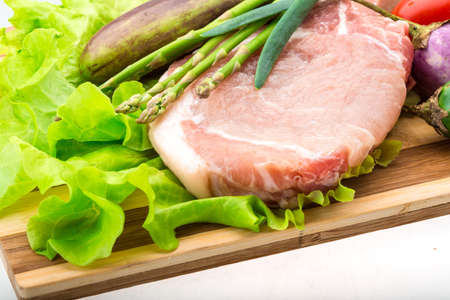 Raw t-bone steak with asparagus and egg-plant photo